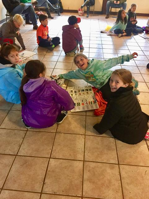 girls sitting on the floor with large paper