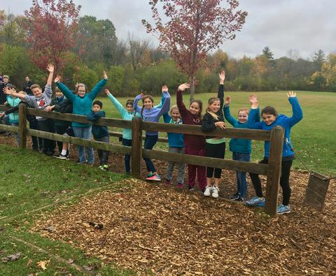 Class lined up at a split rail fence waving at the camera