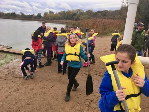 girl wearing a life preserver holding an oar
