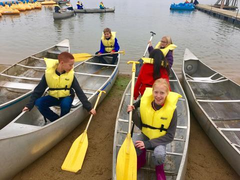 girl in a canoe holding an oar
