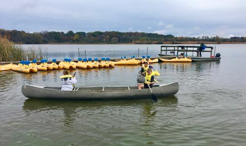 students in a canoe starting to row out onto the water
