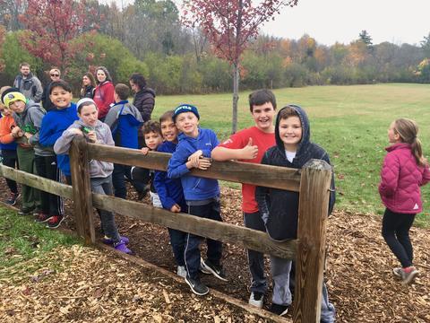 class standing along a split rail fence