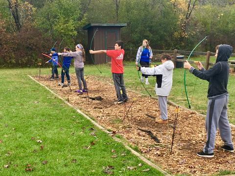 line of students about to release arrows from bows