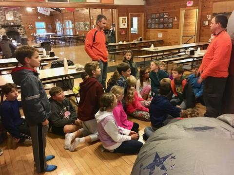 students and teacher listening to a talk from camp duncan employee