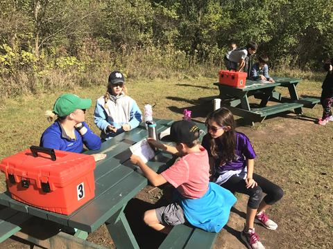 students seated at picnic table with tool box activity