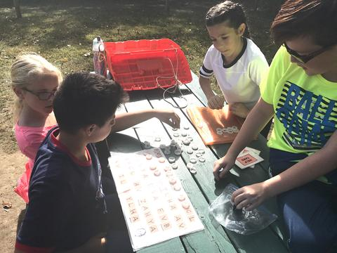 students at a picnic table using bottle caps for an activity