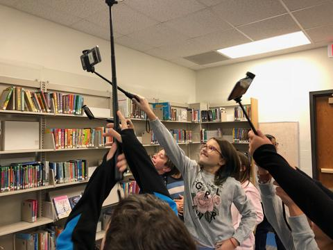 group of students holding their selfie sticks in the air to view image