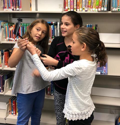 three girls gather around a device