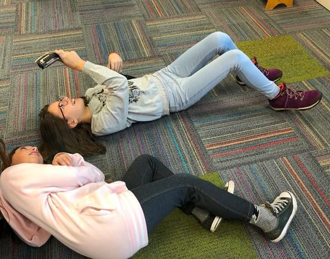 students on floor under their device, looking up