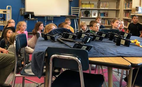students listening to instructions next to the table full of devices