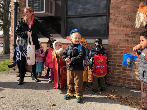 students and teachers standing along building in costumes