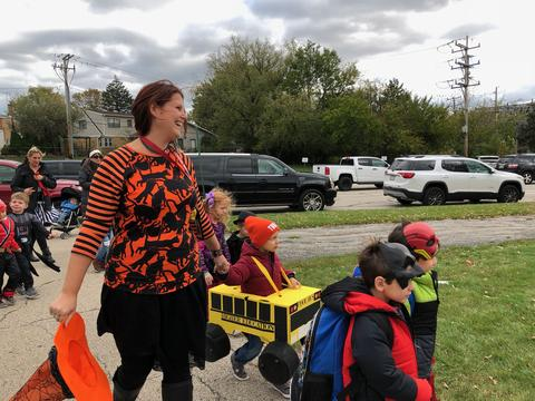 teacher guiding students in the parade