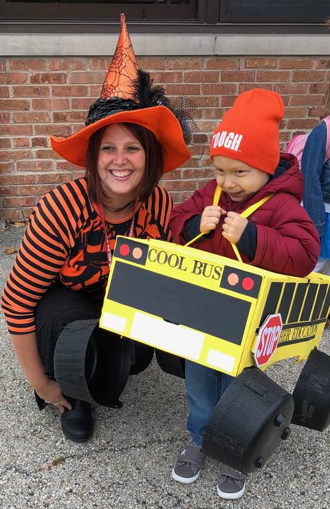 teacher posing with student in a bus costume