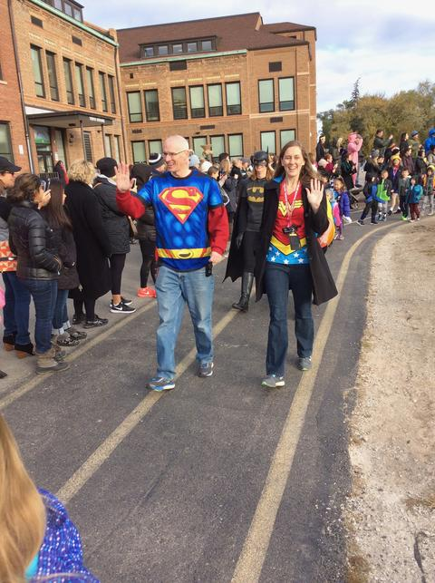 Principal and assistant principal dressed up as superman and wonder woman