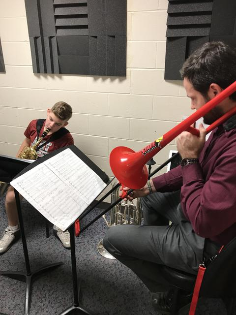 teacher with red trombone playing with student saxophonist