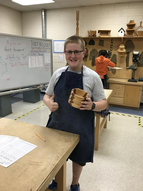 student holding wooden pot