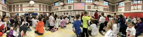 panoramic view of students in the gym for the assembly