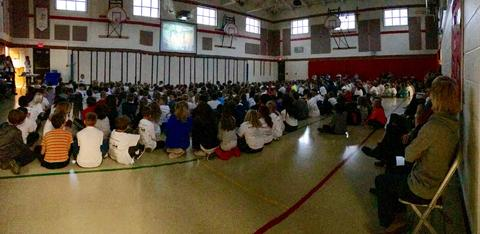 panoramic view of students seated on gym floor watching video