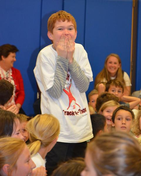 boy standing with hands held up to face expressing happy surprise