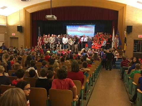 Pledge of Allegiance recited while all stand during assembly in auditorium