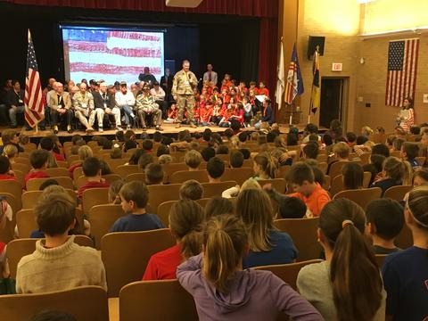 Assembly with veteran on stage addressing audience