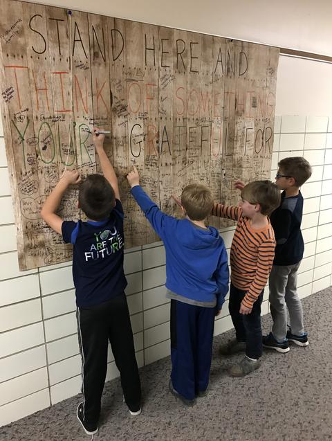 Students signing wall sign at Washington