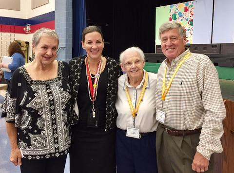 Superintendent posing with several retirees at retiree breakfast