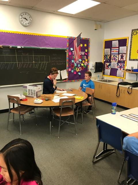 student conferencing with a student at a table