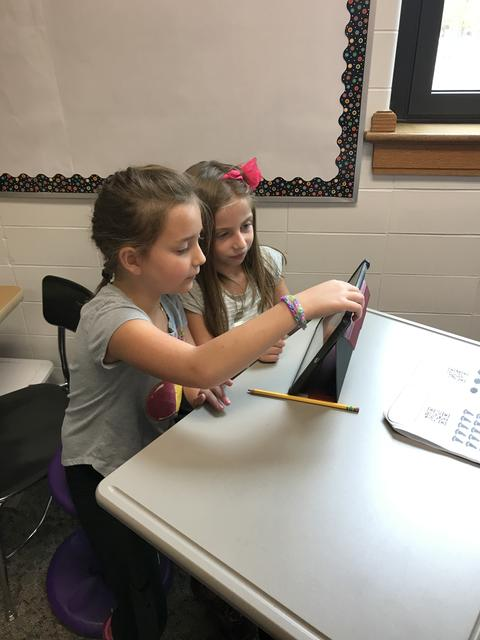 two girls working on ipads