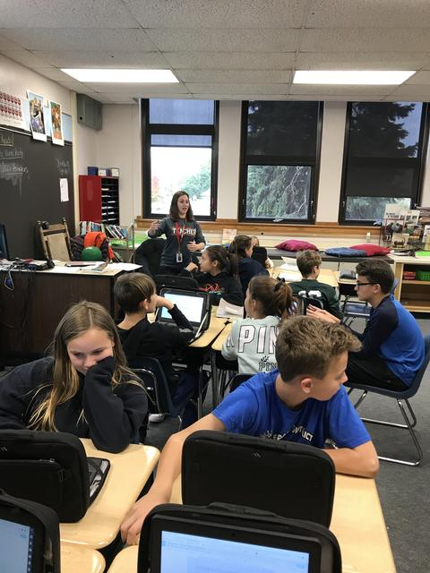 teacher directing students working on chromebooks