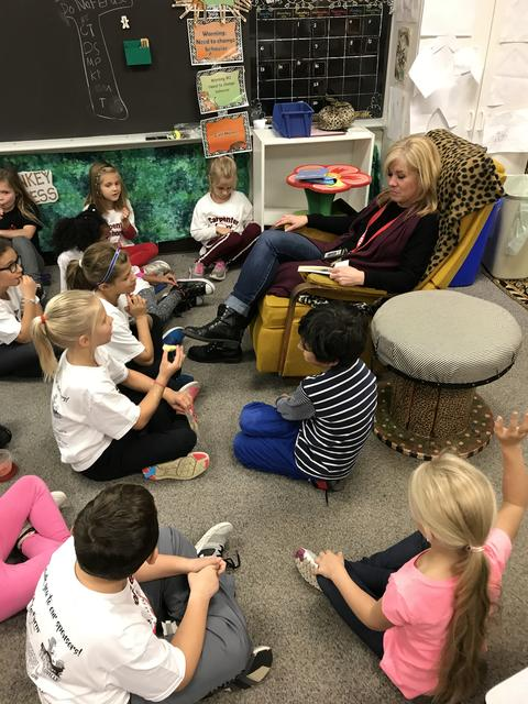 teacher sitting in rocker surrounded by students