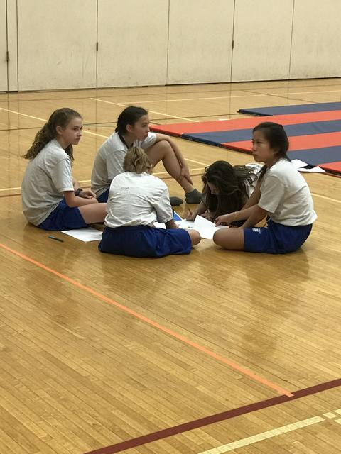 girls sitting in a circle on gym floor