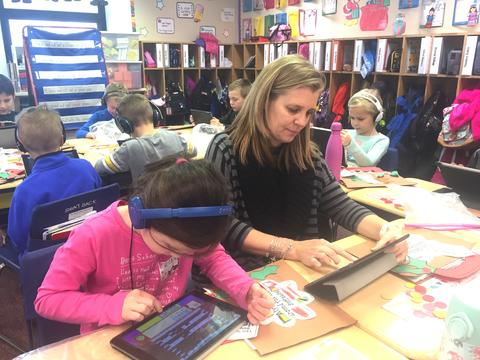 Teacher working with a student on coding on iPads