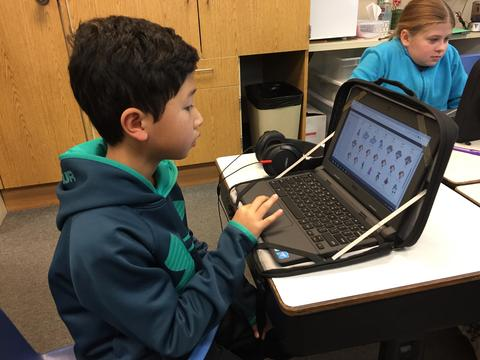 side view of boy and chromebook screen