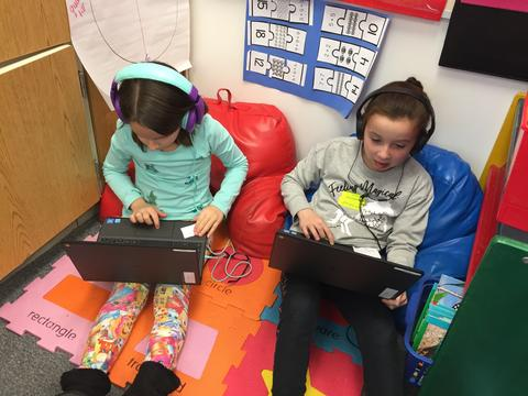 two students sitting on the floor, leaning on bean bag pillows working on coding