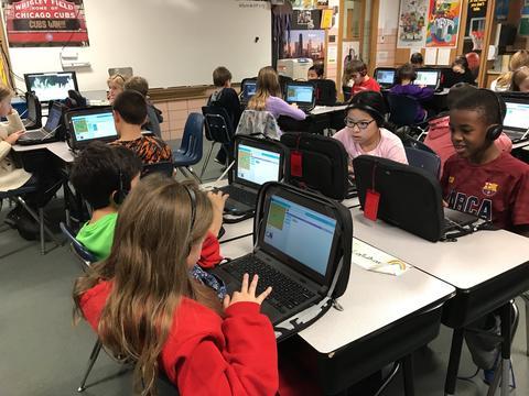 Students at desks coding on chromebooks