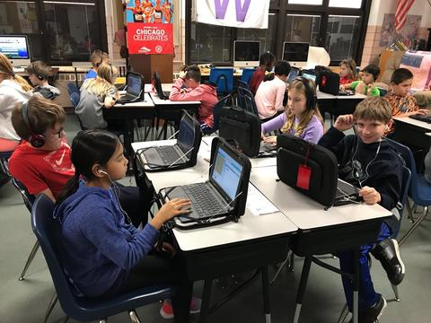 Students coding with one boy smiling for picture
