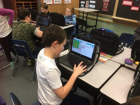 Boy coding on chromebook