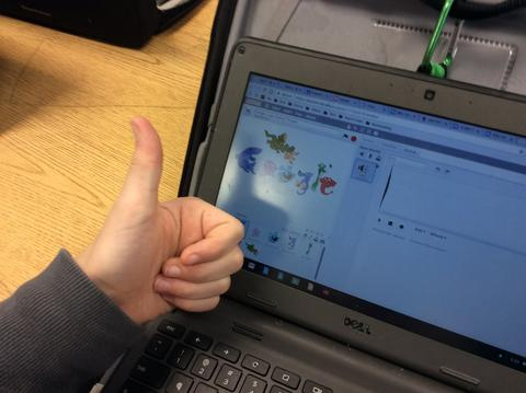 Student giving a thumbs up with his chromebook screen