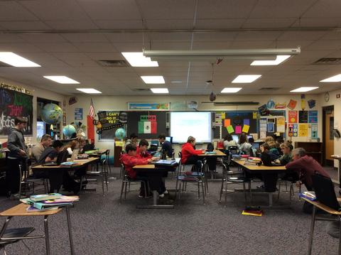 Wide shot of principal and teacher working with students during coding activity