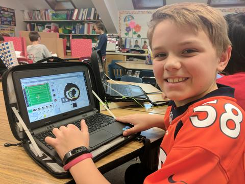Boy smiling for the camera while coding