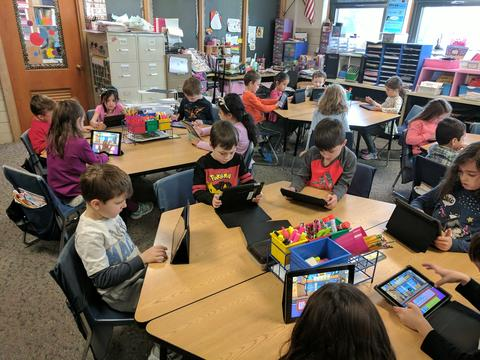 students around tables coding on ipads
