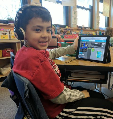 boy turned toward camera with ipad coding activity visible