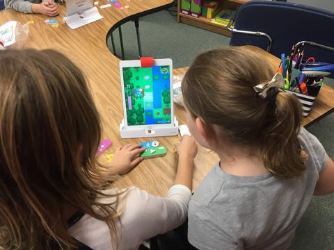 coding on ipad screen in a stand with two students looking on