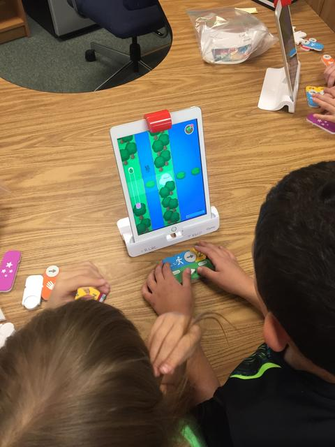 student using ipad in a stand during coding activity
