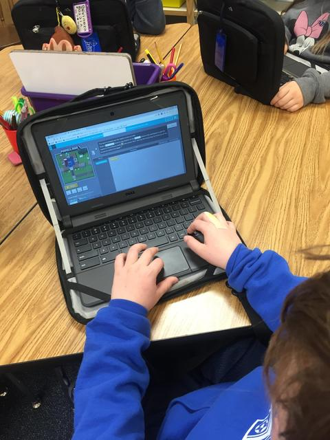 students hands on chromebook keyboard, coding