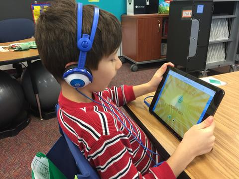 young boy holding up his ipad during coding activity
