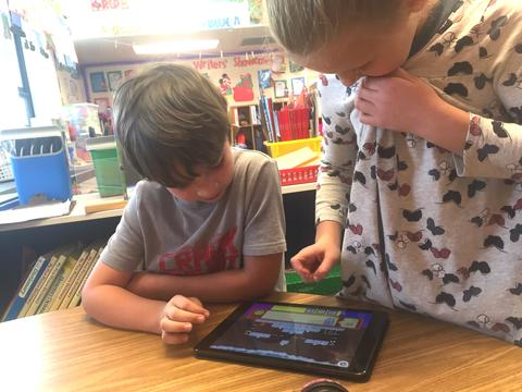 two students coding together on one ipad
