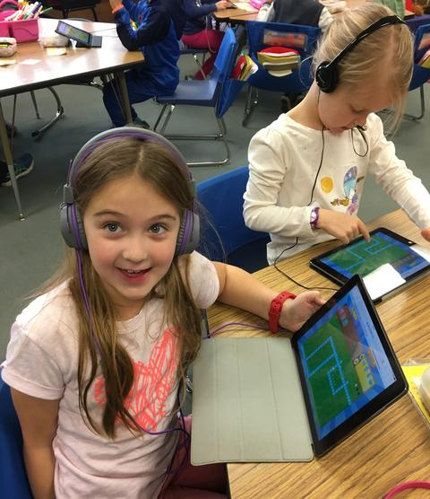 girls smiling hugely at the camera, with her iPad visible