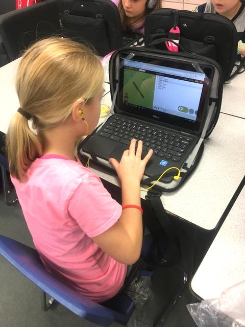 girl coding on chromebook wearing yellow earbuds